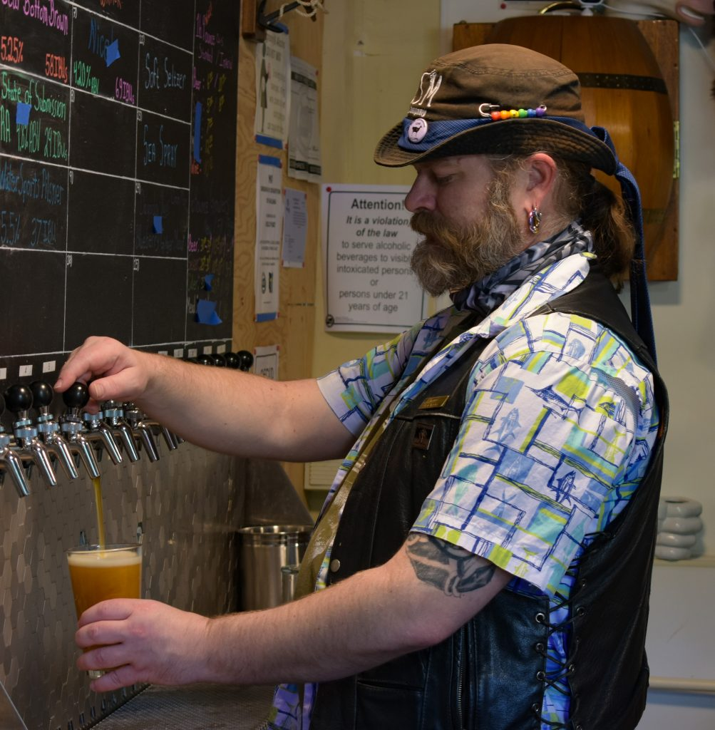 Owner of BDSM Brewing Company, Billy, pouring a golden pint of beer